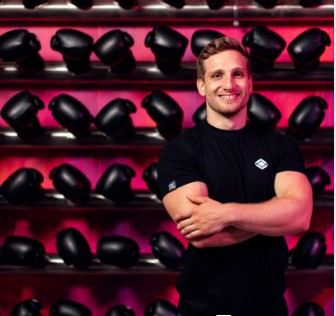 Friendly fitness professional posing in front of boxing gloves.