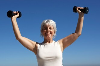 Woman triumphantly lifting dumbbells.