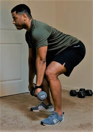 Staunton Personal Trainer Donte Collins demonstrates a dumbbell clean and press exercise
