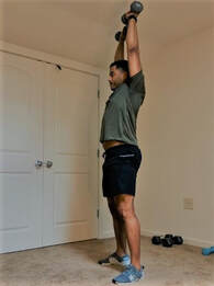 Staunton Personal Trainer Donte Collins demonstrates the final phase of a dumbbell clean and press exercise