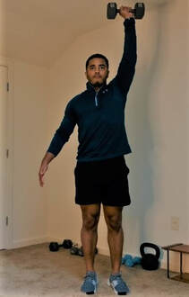 Staunton Personal Trainer Donte Collins demonstrates contralateral lateral lunge to overhead press exercise, phase 3.