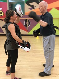 Boxing coach and client, taking a break during a cardio workout, high fiving one another.
